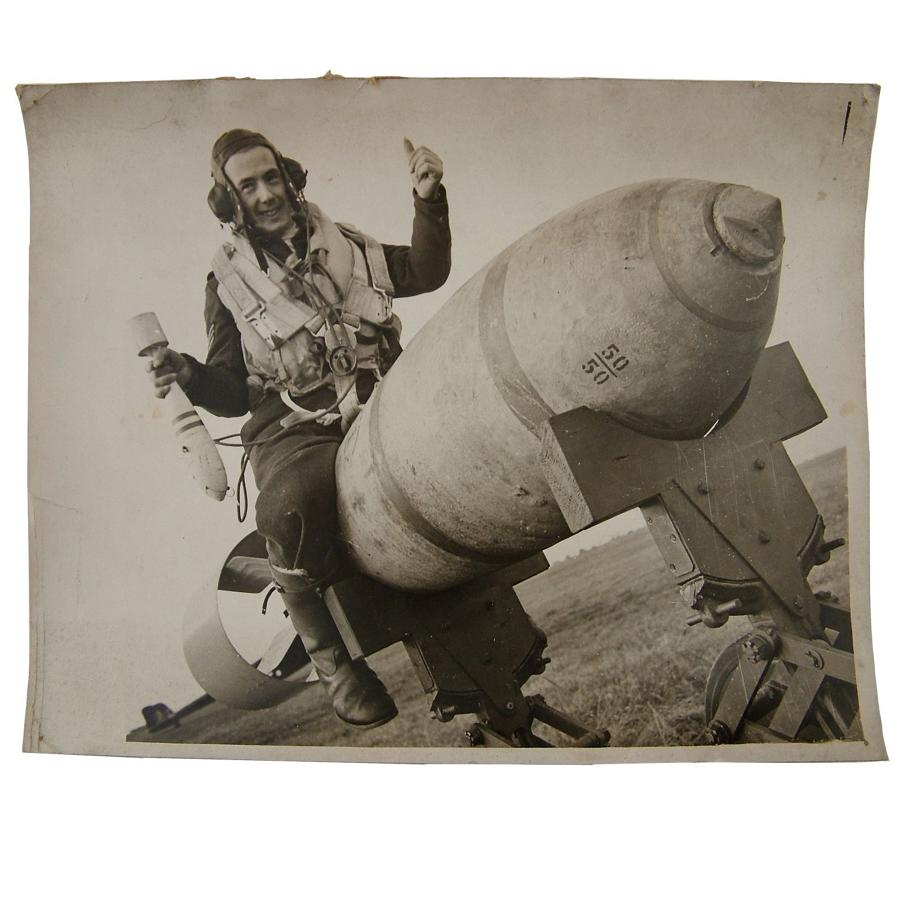 Press photo - RAF airman astride a large bomb