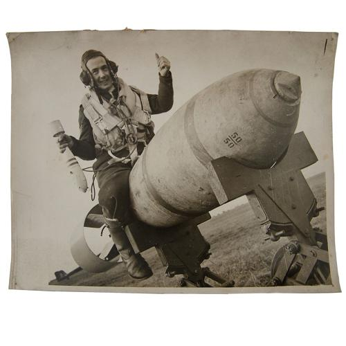 Press photo - RAF airman astride a large bomb